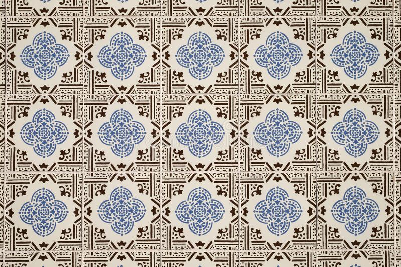 Den gamla väggen med den traditionella portugisiska dekoren belägger med tegel azulezhu i blåa och bruna signaler på en beige bak arkivfoton