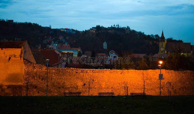 Den gamla väggen som omger den gamla Brasov staden Svart kyrka i bakgrunden Bild på den blåa timmen arkivfoton