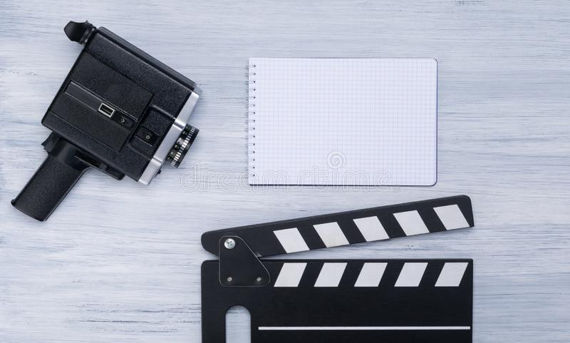 Den gamla videokameran, dubblerar för skytte och en anteckningsbok med ett ställe för att skriva på ett ljust - grå bakgrund royaltyfria bilder