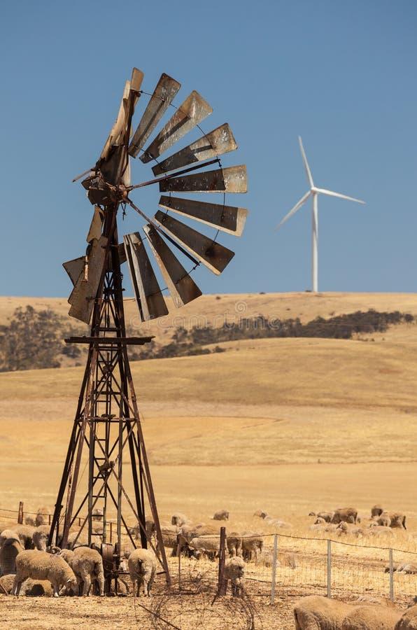 Den Gamla Vindpumpen Och Nya Vindgeneratorer Förvred Vid Varm Luft. Södra Australien. Royaltyfri Foto