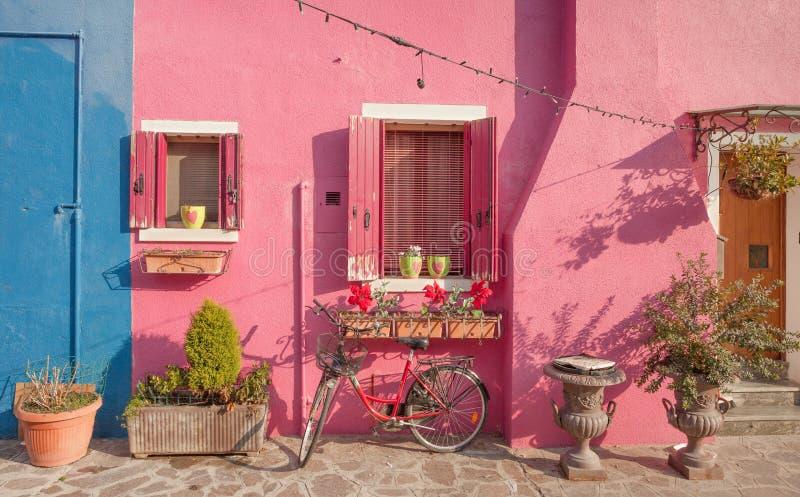 Den gamla violetta cykeln parkerade länge en yttre vägg i den Burano ön arkivbild
