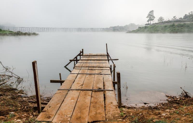 Den gamla wood bron för sikt in i floden med dimma royaltyfri foto