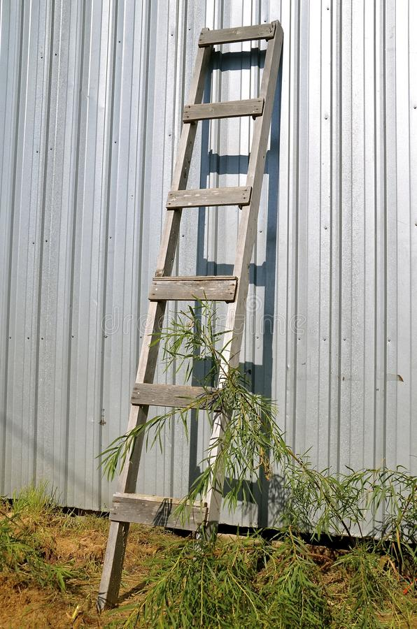 Den gamla wood stegen lutar mot stålbyggnad royaltyfri fotografi