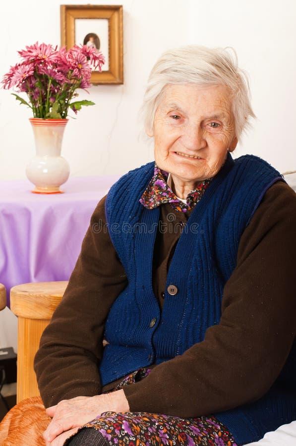 Den gammalare ensamma kvinnan sitter på underlaget royaltyfria foton