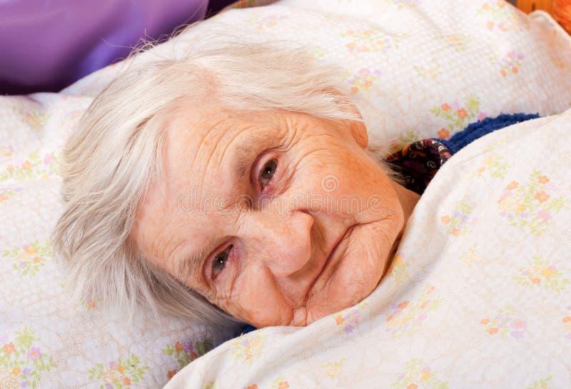Den gammalare ensamma kvinnan vilar i sängen royaltyfria bilder