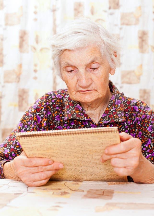 Den gammalare lyckliga kvinnan läste något från boken royaltyfri fotografi