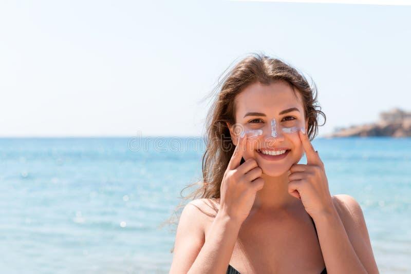 Den garvade kvinnan skyddar hennes framsida med solkr?m fr?n solbr?nna p? stranden arkivbild