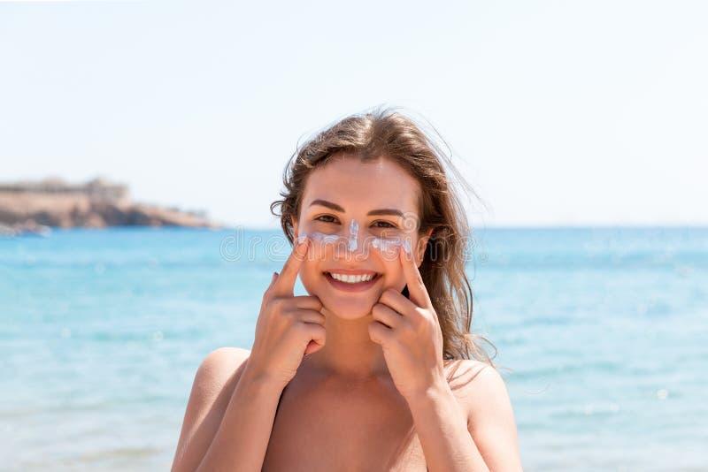 Den garvade kvinnan skyddar hennes framsida med solkr?m fr?n solbr?nna p? stranden royaltyfri bild
