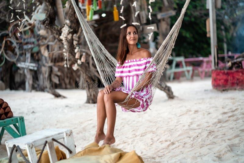 Den garvade unga flickan har vilar att sitta i hängmattan och att se till sidan på bakgrunden av det kust- lägret royaltyfria foton