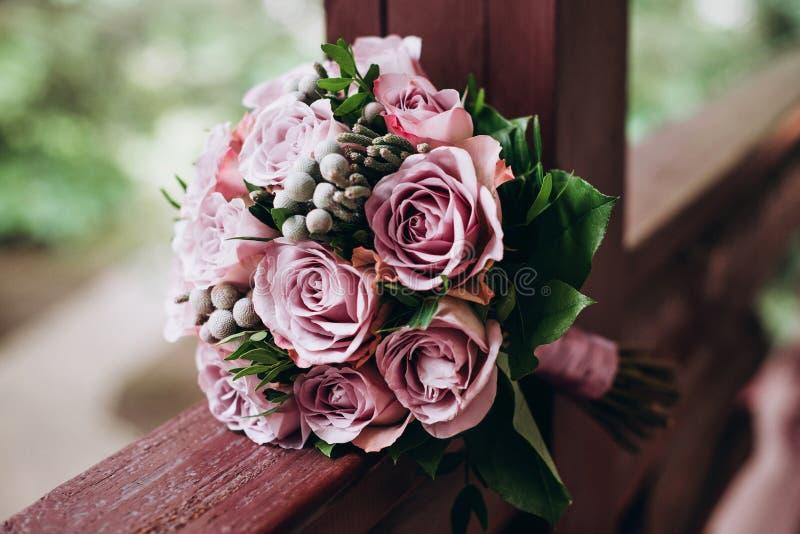 Den gifta sig buketten av fästmön från rosorna av mjuka toner ligger på en träbalustrad royaltyfri foto