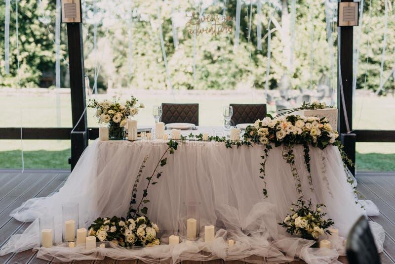 Den gifta sig dekoren på öppen restaurangterrass med vita rosor och stearinljus royaltyfri fotografi