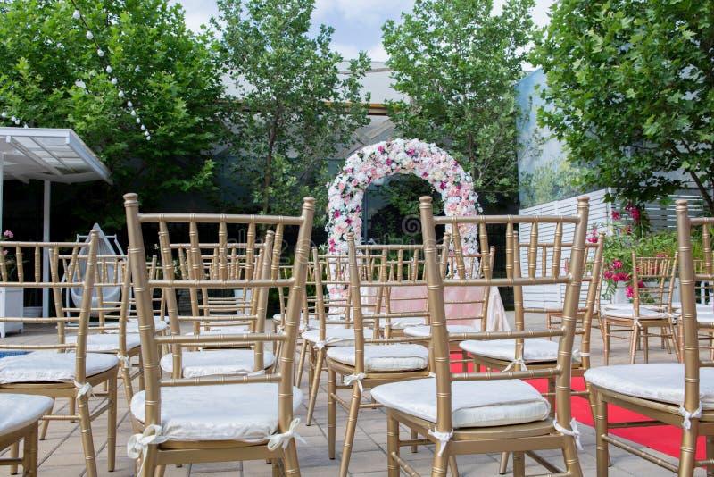 Den gifta sig mötesplatsen med en blommabåge arkivbild