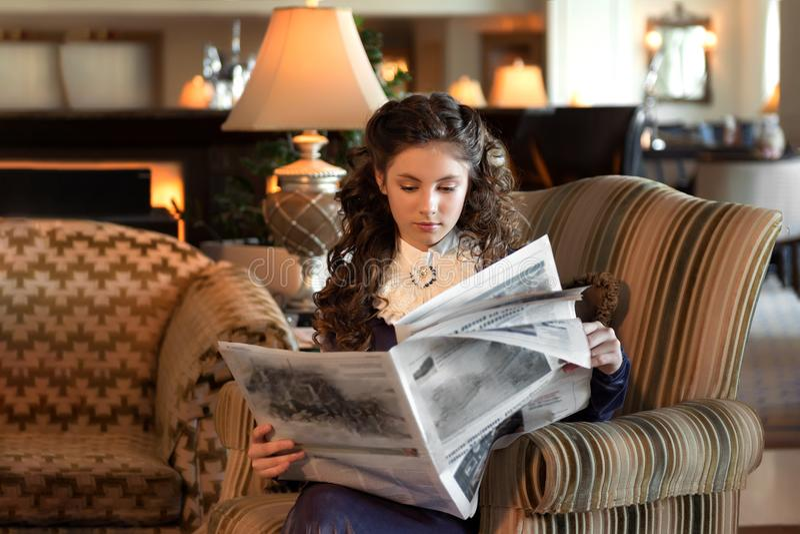 Den giftasvuxna flickan sitter i en gammalmodig fåtölj som är iklädd klär en tappningsammetlila, och läsa en tidning fotografering för bildbyråer