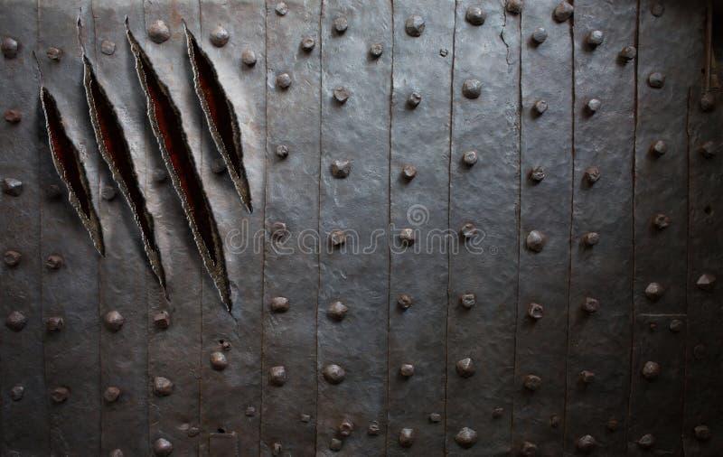 Den gigantiska jordluckraren skrapar på metallväggen eller dörr royaltyfri fotografi