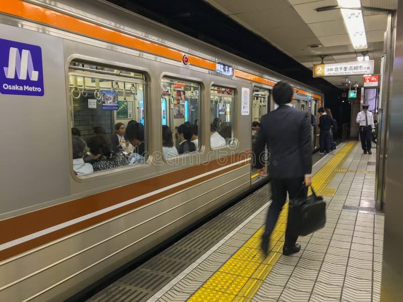 Den gjorda suddig japanska affärsmannen går på vid en drevplattform i Osaka, Japan arkivfoton