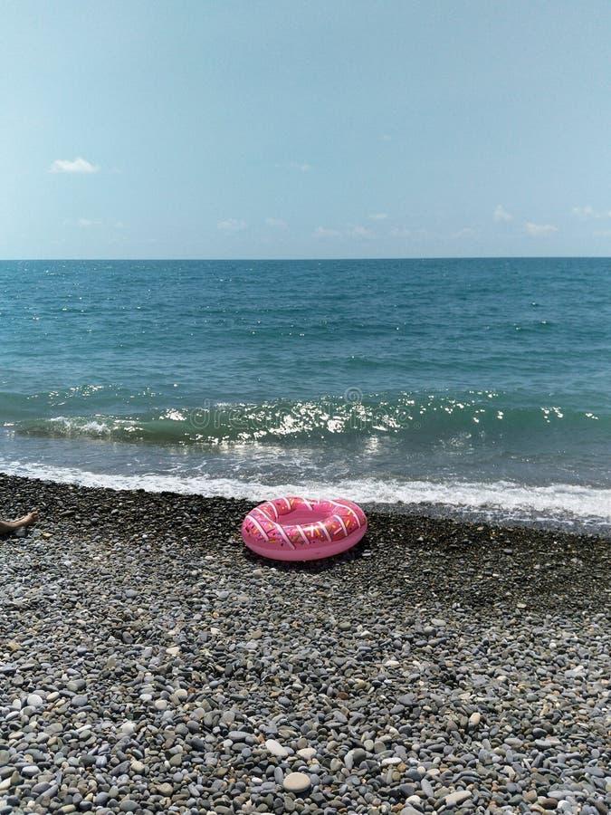 Den glömda uppblåsbara cirkeln ligger på kusten, en räddningslina i form av en munk, barn arkivfoton