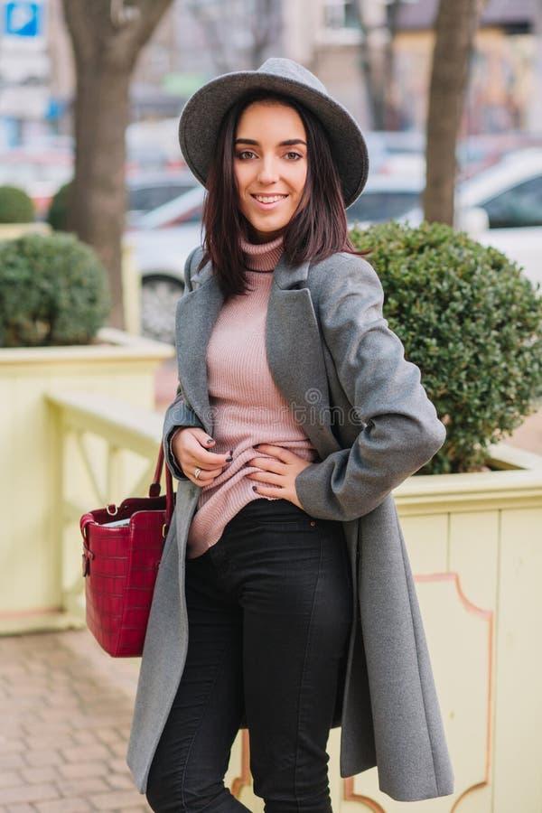 Den glade charmiga unga kvinnan med brunetthår i det långa gråa laget, hatt som går på gatan i stad, parkerar Elegant framtidsuts royaltyfri foto