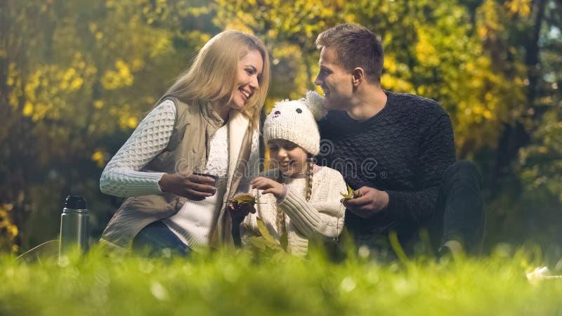 Den glade familjen som har gyckel i höst, parkerar och att spendera fritid tillsammans, lyckligt fotografering för bildbyråer
