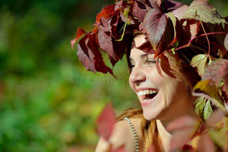 Den glade flickan i en krans av röda och gröna sidor skrattar glatt på den gröna bakgrunden på en solig dag fotografering för bildbyråer