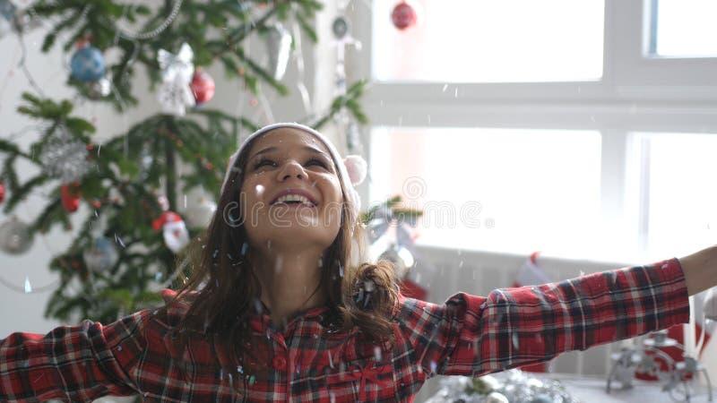 Den glade flickan i jultomtenlock kastar upp konfettier nära julgranen vid fönstret arkivfoton