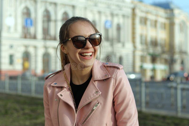 Den glade flickan skrattar contagiously, medan gå runt om staden arkivbilder