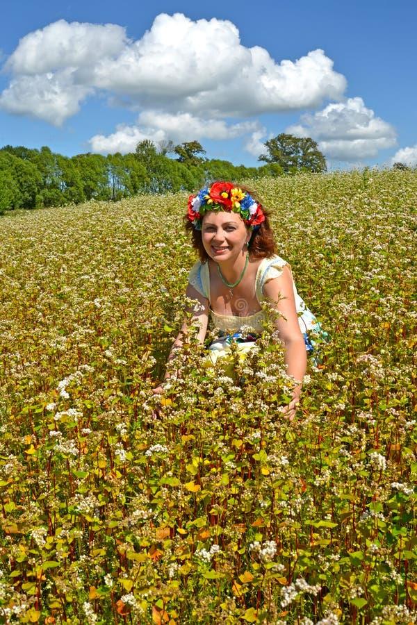 Den glade kvinnan av genomsnittliga år med en krans på huvudet i te som blomstrar bovetefältet arkivbilder
