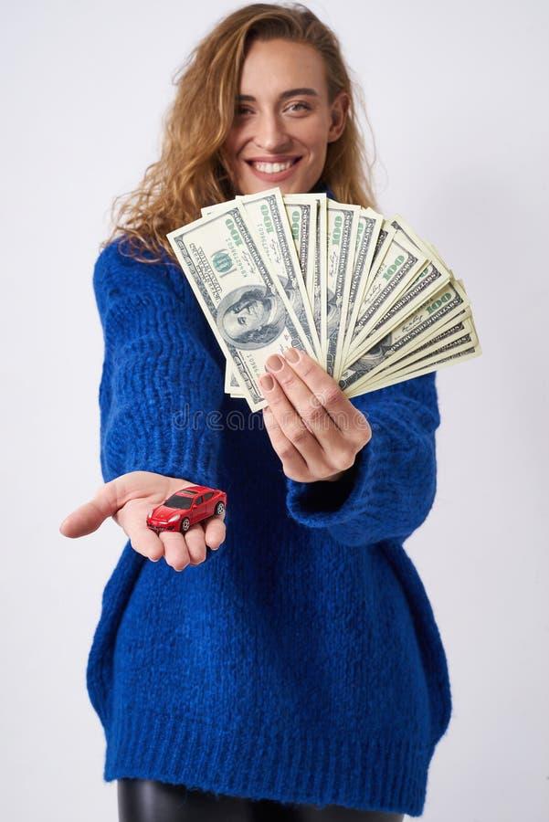 Den glade kvinnan erbjuder att köpa en bil royaltyfri bild