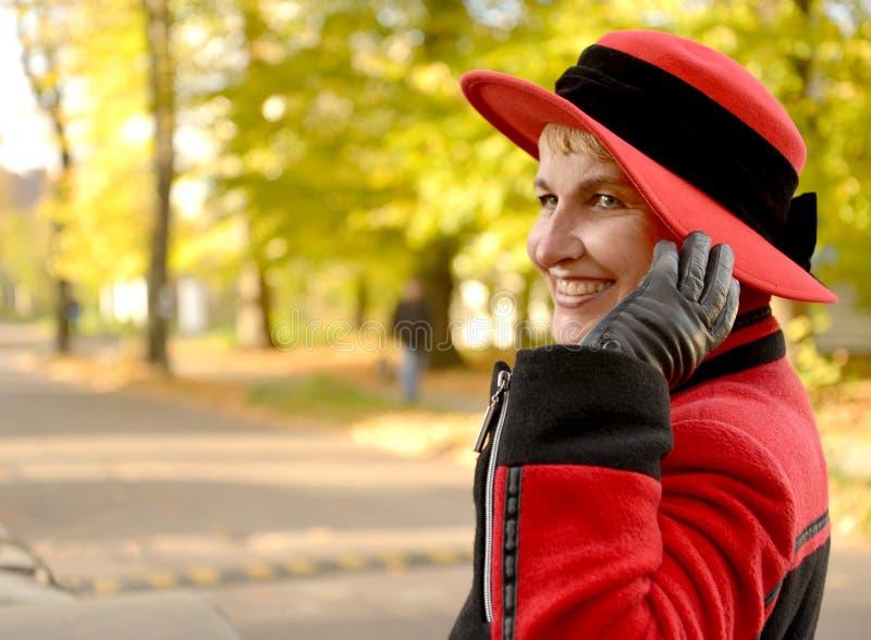 Den glade kvinnan rymmer en hatt med en hand på höstgatan royaltyfri foto
