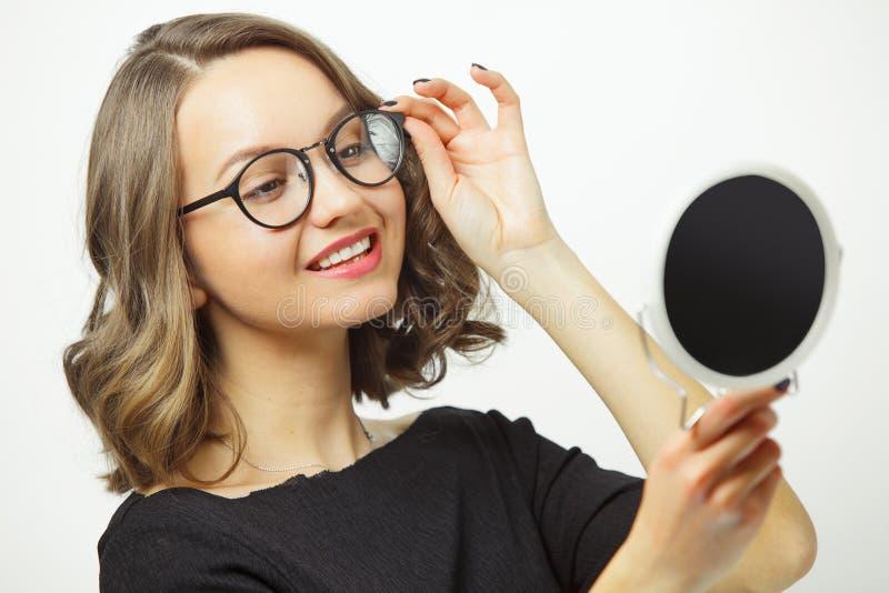 Den glade kvinnan som försöker på exponeringsglas på spegeln och lyckligt ler, har ett lyckligt uttryck som tillfredsställs med v fotografering för bildbyråer
