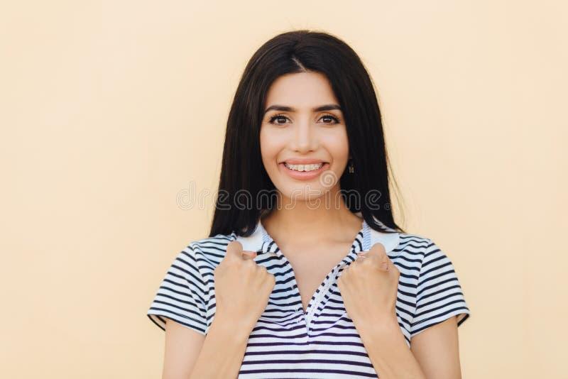 Den glade kvinnlign med angenämt leende, håller händer i nävar, bär hänglsen på tänder, har mörkt rakt hår som isoleras över beig arkivfoto