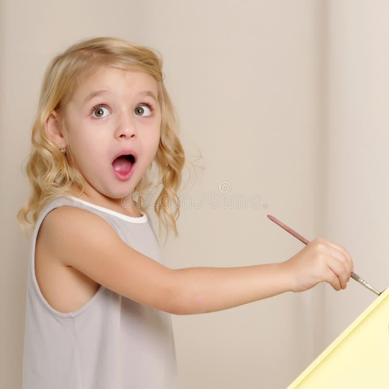 Den glade lilla flickan drar en borste arkivbilder