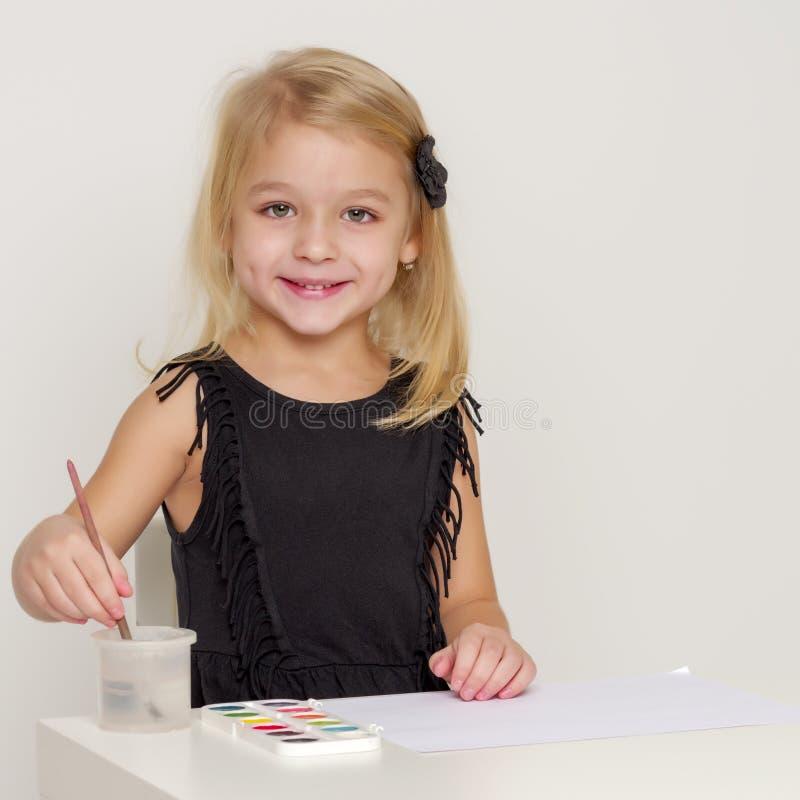 Den glade lilla flickan drar en borste arkivbild