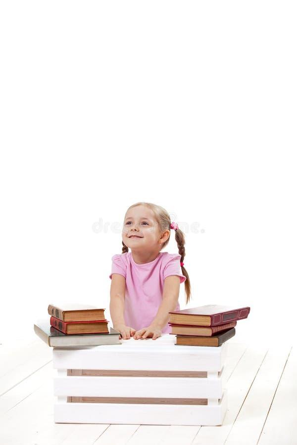 Den glade lilla flickan med böcker sitter på ett vitt golv arkivfoton