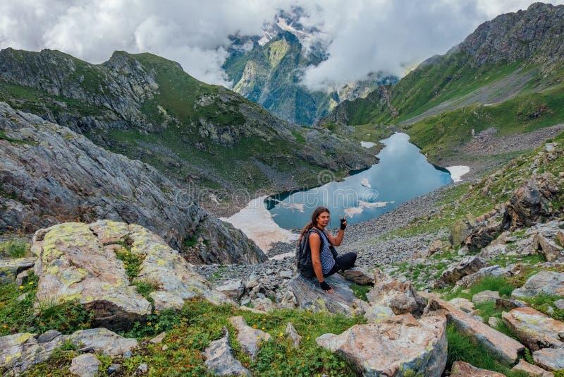 Den glade lyckade manturisten med segergest vaggar på på berg nära den kalla bergsjön royaltyfri fotografi