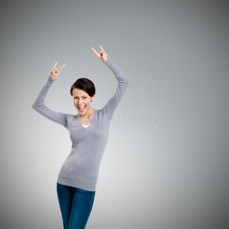 Den glade nätta kvinnan sätter upp henne händer med två fingrar som pekas upp fotografering för bildbyråer