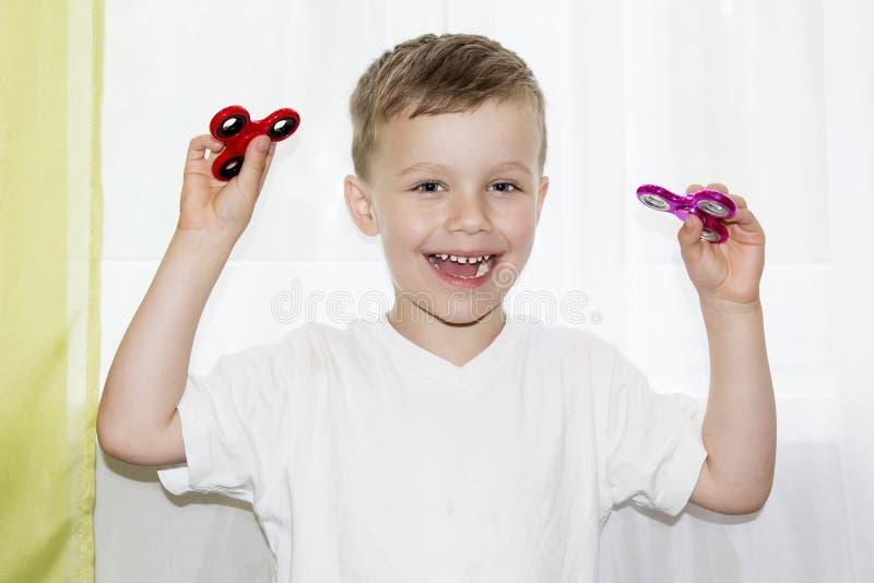 Den glade pojken ler och rymmer i hans spinnare för hand två hemmastatt Barn som spelar med två rastlös människaspinnare royaltyfri bild