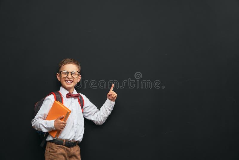 Den glade pysen med en portfölj står på en svart bakgrund med en bok i hans händer lyckligt barn studenten som pekar till fotografering för bildbyråer