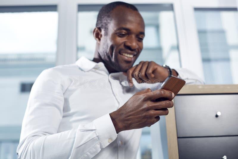 Den glade stilfulla afrikanska mannen surfar internet genom att använda smartphonen royaltyfria foton