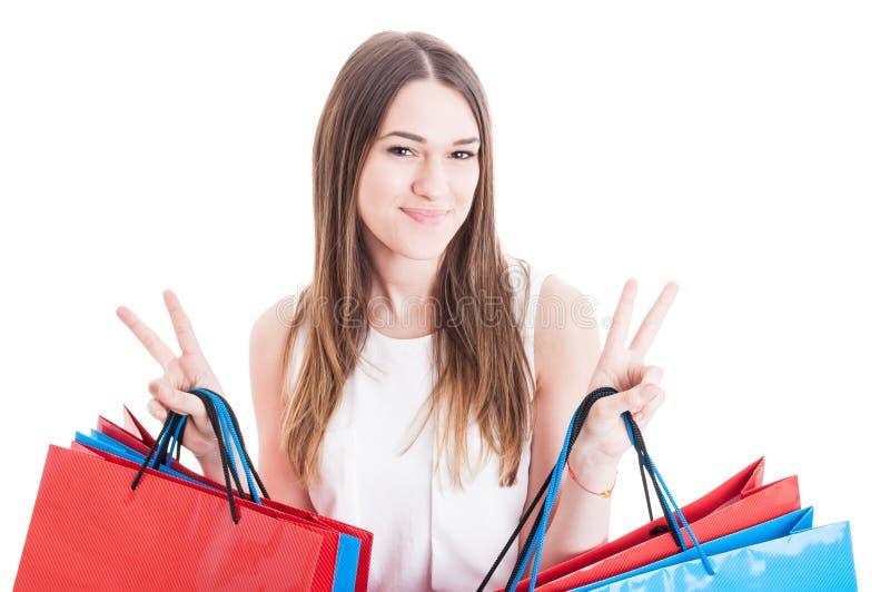 Den glade unga flickan som gör dubbel seger för shopping och för visning, undertecknar fotografering för bildbyråer
