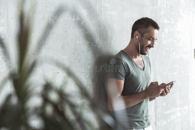 Den glade unga grabben lyssnar till musik genom att använda hans telefon royaltyfri bild