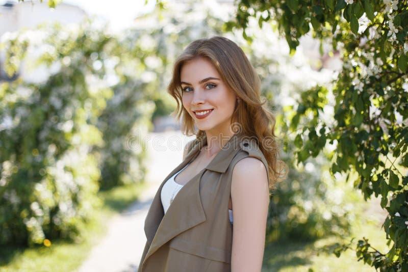 Den glade unga kvinnan med ett härligt leende i en trendig sommar tilldelar en stilfull t-skjorta är stå och se kameran royaltyfri bild