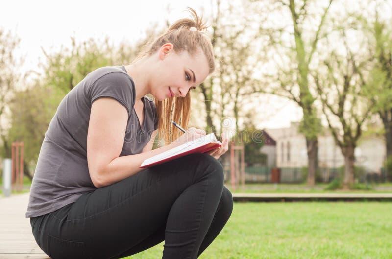 Den glade unga kvinnlign i vår parkerar handstil i hennes dagbok fotografering för bildbyråer