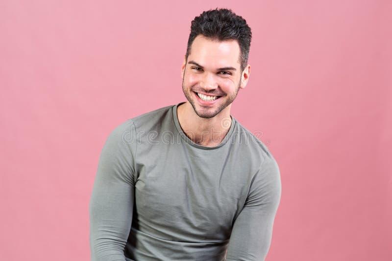 Den glade unga mannen av en sportkonstitution skrattar och ser glatt in camera horisontalstående på bakgrund royaltyfri bild