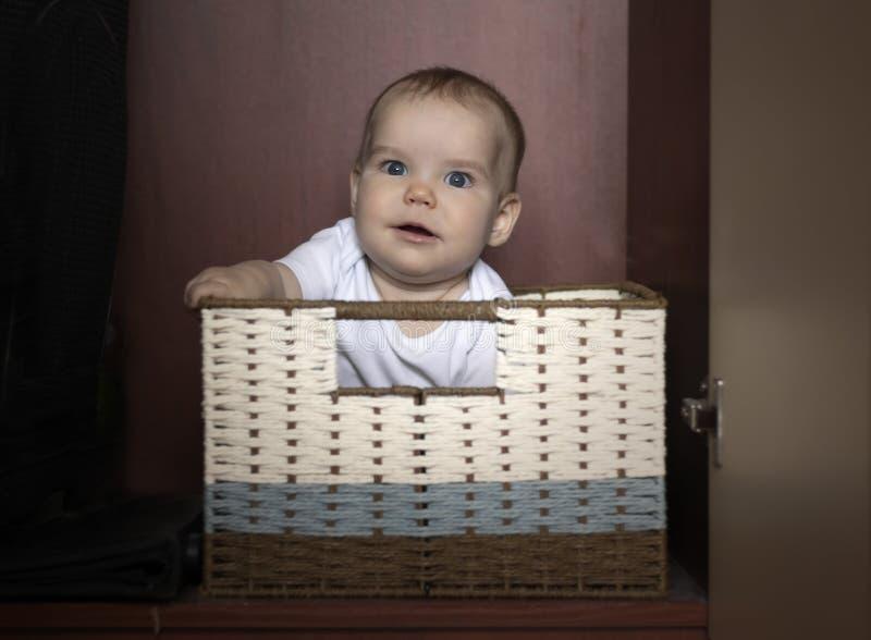 Den glade ungen sitter i en ask i en vide- korg I garderoben för lagring på en mörk bakgrund Begrepp av lagring royaltyfri bild
