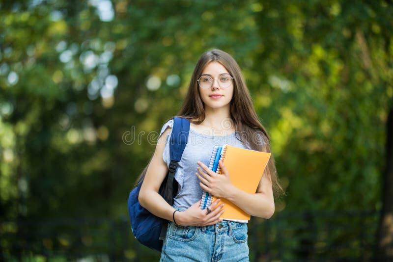 Den gladlynta attraktiva unga kvinnan med ryggsäcken och anteckningsböcker som in står och ler, parkerar arkivfoto