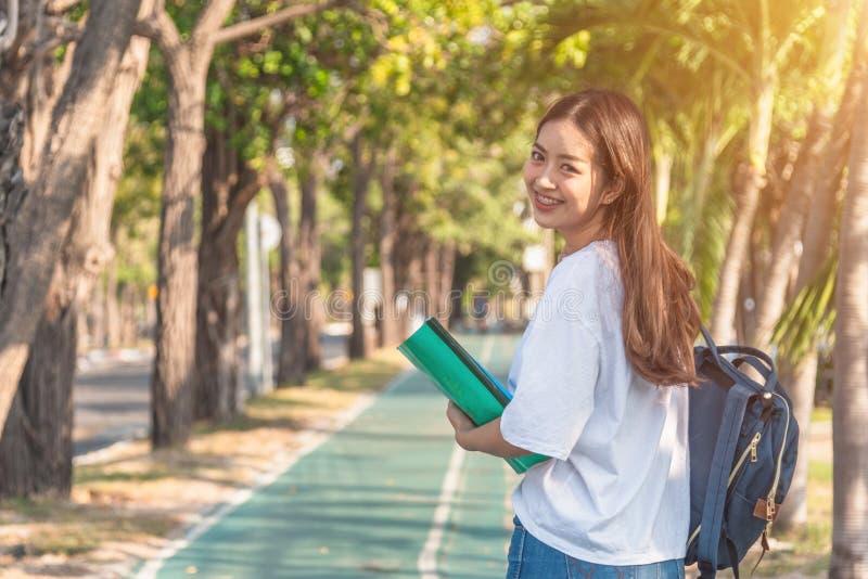 Den gladlynta attraktiva unga kvinnan med ryggsäcken och anteckningsboken och anseendet i parkerar arkivbild
