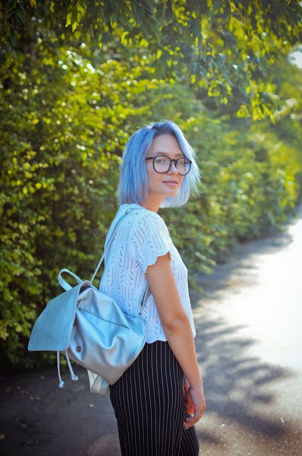 Den gladlynta blått-haired flickastudenten med en portfölj av försilvrar material royaltyfri fotografi
