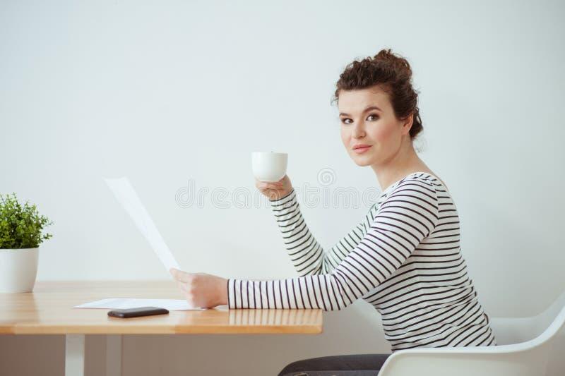 Den gladlynta brunettflickan tycker om den varma drinken fotografering för bildbyråer