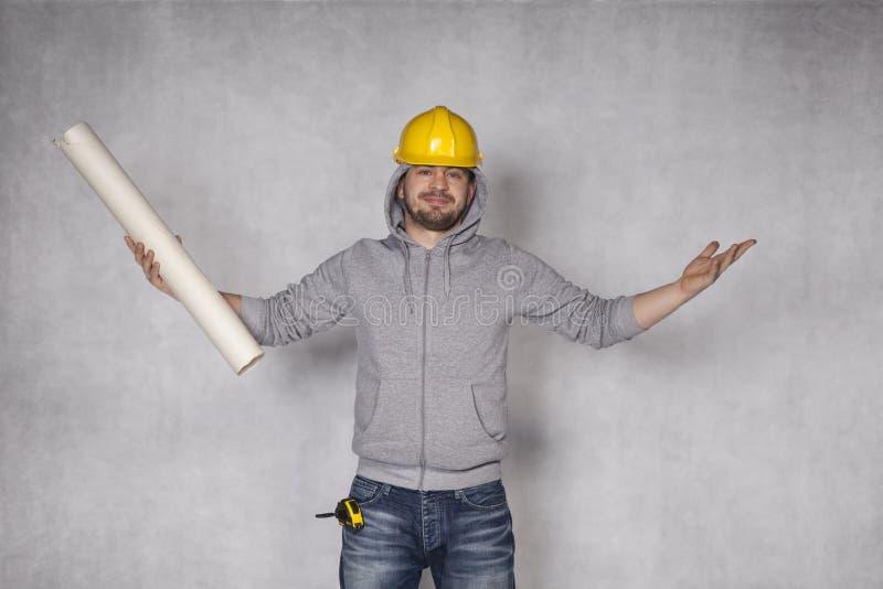 Den gladlynta byggmästaren kastar upp hans händer i en gest av segern arkivfoton
