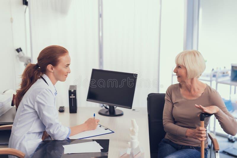 Den gladlynta damen mottar medicinsk behandling från kvinnlig kirurg arkivfoton